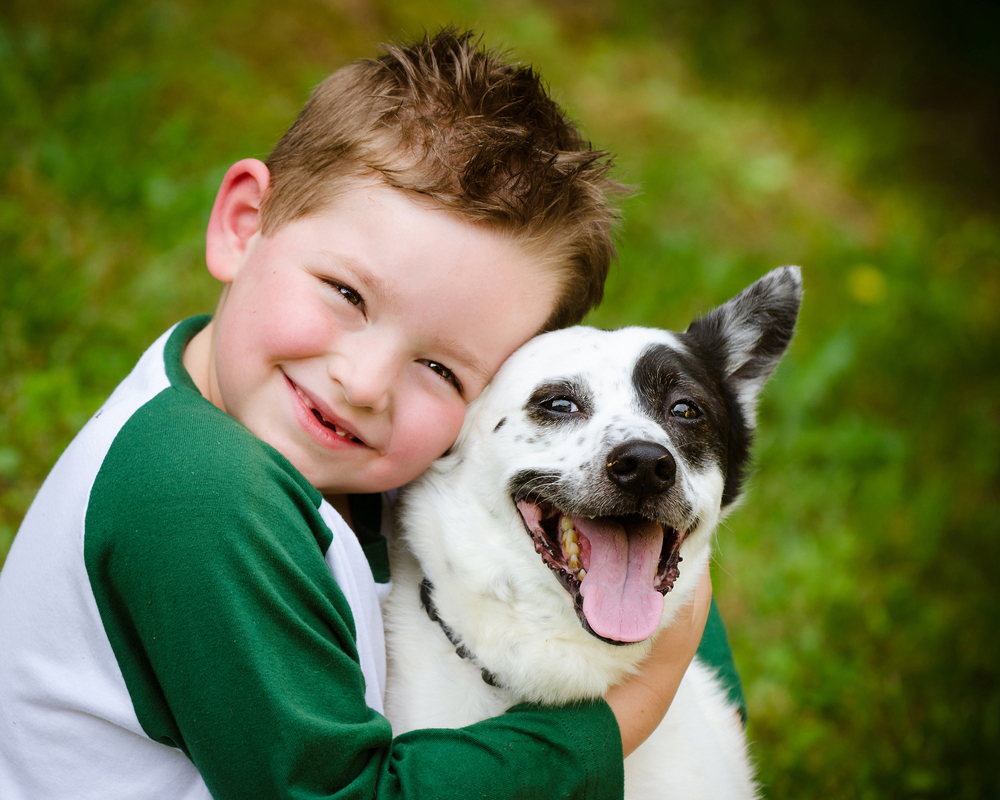 young boy holding his puppy